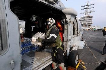 米空母レーガンで救援物資を積み込む兵士