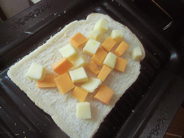 パンにチーズを乗せてグリルに入れる