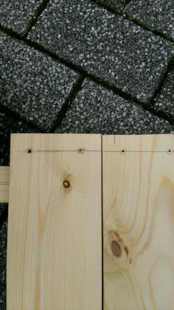 扉の枠の上の木材にドリル