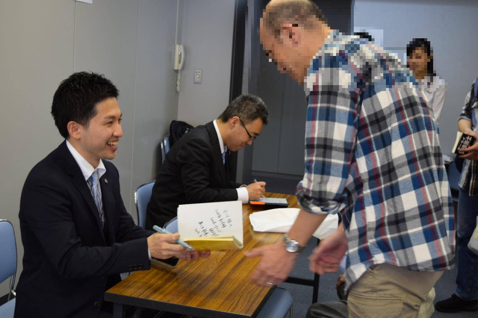 黒沢先生が本を渡しているところのモザイク
