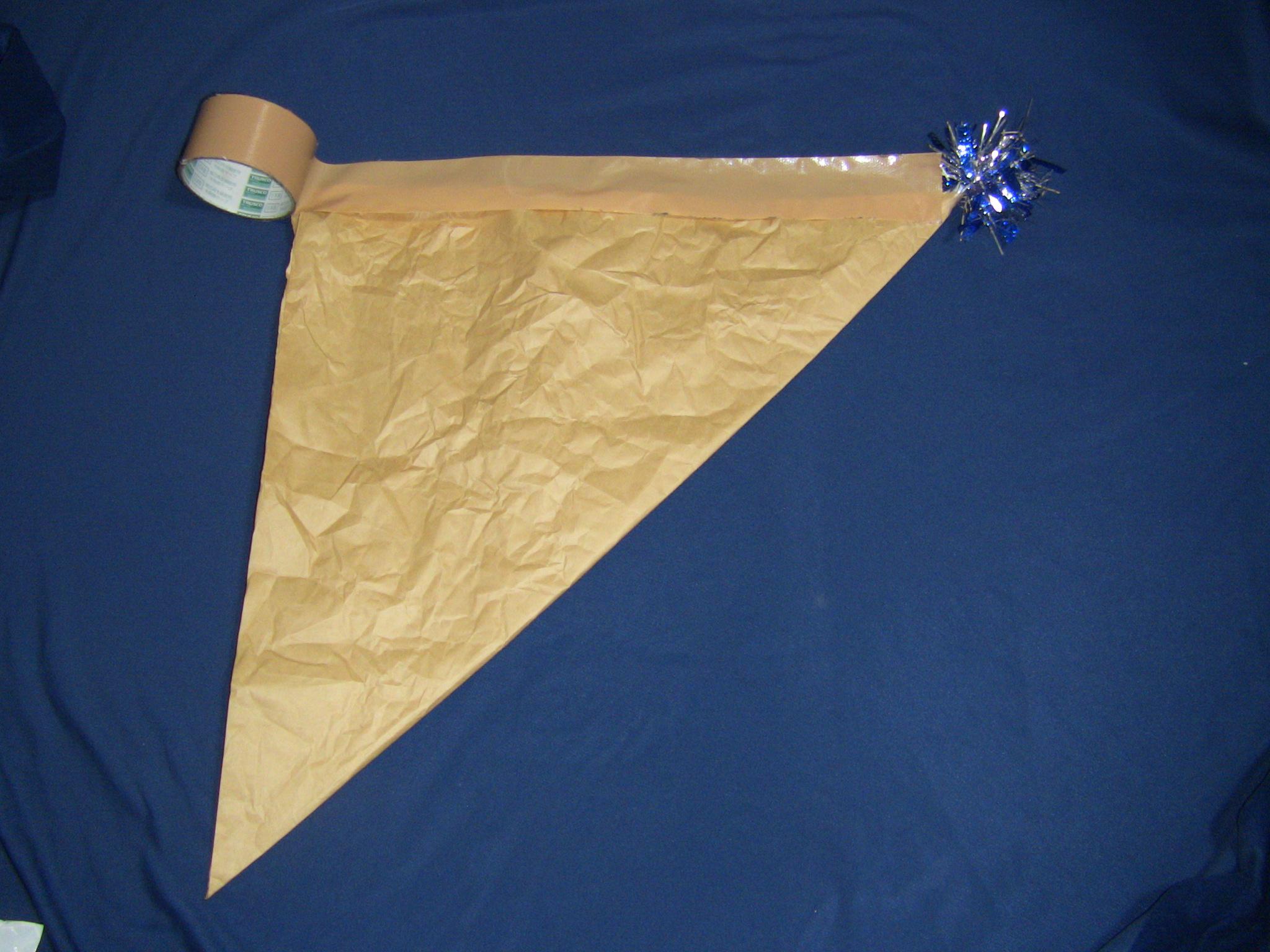 クラフト紙で魔法使い帽子1辺をテープで留める1