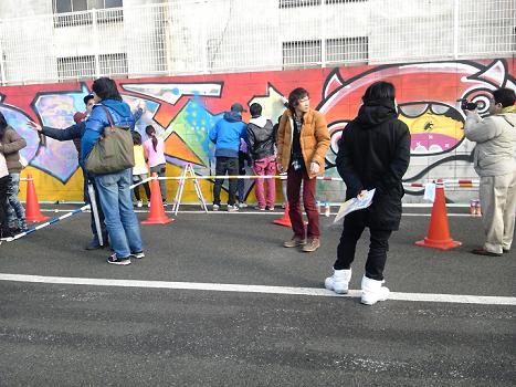 2 大勢の人たちが集まって壁画作りをやってます
